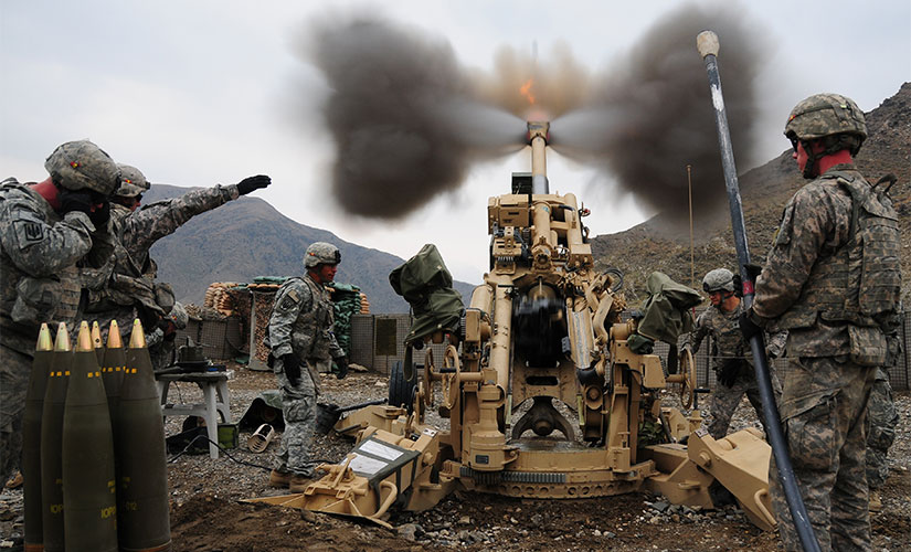 A group of soldiers stand around a tan machine, which is in the process of firing an explosive. There are mountains in the background, and ammunitions set up beside the machine.