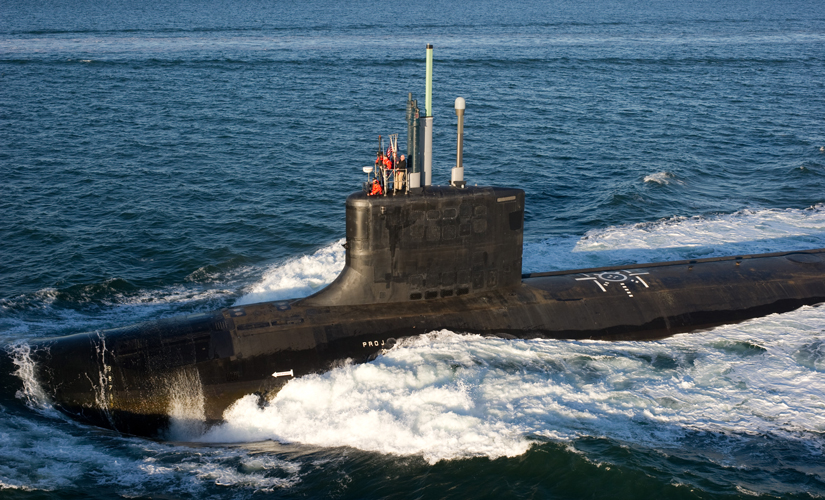 Image of part of the submarine, which is over the surface of the water. The water is deep blue and it is a sunny day out.