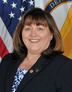 Image of JoEtta Fisher, a woman with light brown hair and bangs. She sits in front of two flags (one being the American flag) and smiles at the viewer.