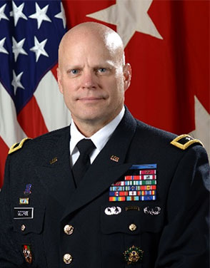 Picture of Major General John A. George. MG George is seated in front of the US flag and wears an army uniform with badges and insignia. He is smiling with a closed mouth at the viewer.