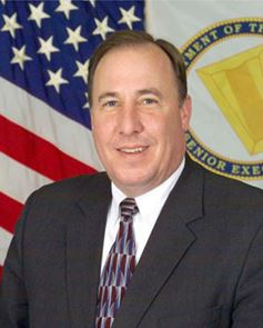 Image of a man (John Hedderich, III) seated in front of the American Flag. He wears a gray suit and has a muti-colored, red and blue tie on. He has blue eyes.