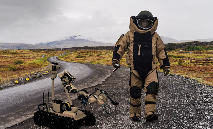 EOD Warrior in full suit approaching on right side of image. MTRS-2 Robot on left side of image. Both are on a gravel road in a field with low scrub bushes and grasses. Hills in the background. The day is cloudy.