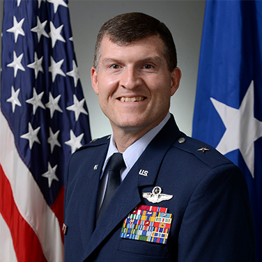 Image of Brig Gen Hinote, USAF. Brig Gen is in a military uniform and stands before the American flag, smiling at the viewer. He has short cropped hair.
