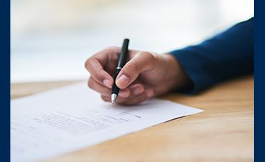 Female African American hand holding a professional black pen writing on a piece of paper which is placed on a natural wood desk.