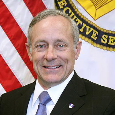 Image of Richard De Fatta, a Caucasian male. He is seated before a U.S. flag and is gazing at the camera with a smile on his face. He wears a dark suit and has a purple tie.
