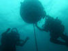 Mine Warfare; Image of two scuba divers underwater interacting with an circular mine