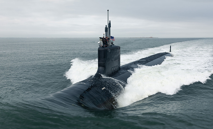 Image of a Submarine partially submerged. A few people stand at the top of the submarine, surrounding a metal pole - Joint USW Technology Spring Conference