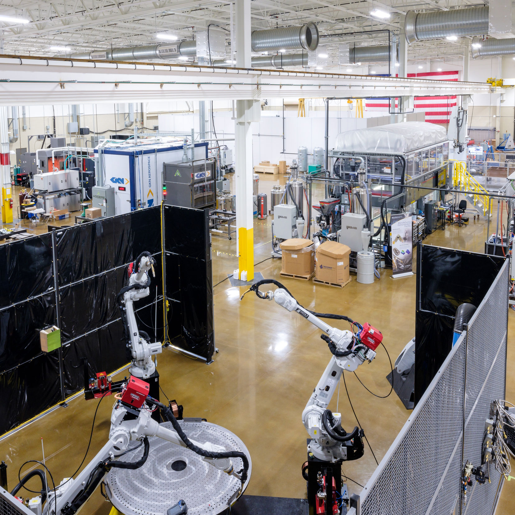 Image of the Manufacturing Demonstration Facility in Knoxville, TN which shows large ware-house facility with numerous large robotic-like machines. The floor is a light colored wood and the ceiling is while with bright long lights.