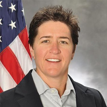 Image of Adele Ratcliff. A woman with short brown hair stands in front of an American flag and a gray background. She has a dark blazer on and a gray shirt. She has an open mouth smile.