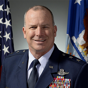 Image of Maj Gen Mike Fantini. Fantini is in front of the American and USAF flags in his blue military uniform. She has an open mouth smile and numerous badges and insignia on his uniform.