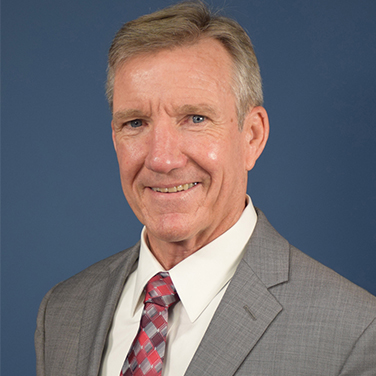 "Image of Herbert J. ""Hawk"" Carlisle. Gen. Carlisle is standing in front of a blue screen. He is smiling at the viewer and wears a gray jacket with a red and gray tie."