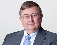 Image of Terry Elling, a man who is seated facing the camera. He has a closed mouth smile and wears a gray suit with a blue tie.