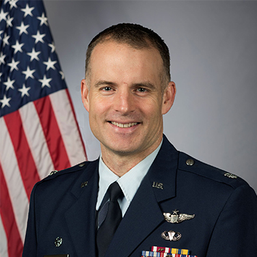 Image of Lt Col Brian Stiles, USAF. Stiles is seated before an American flag. He has an open mouth smile, has short hair, and is wearing an Air Force uniform with buttons and insignia.