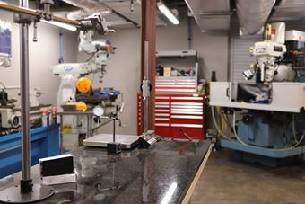 Image of SOFWERX's Foundry; a large open room with concrete floors and large machinery. In front of the viewer is a table which sits a scale and other test instruments.