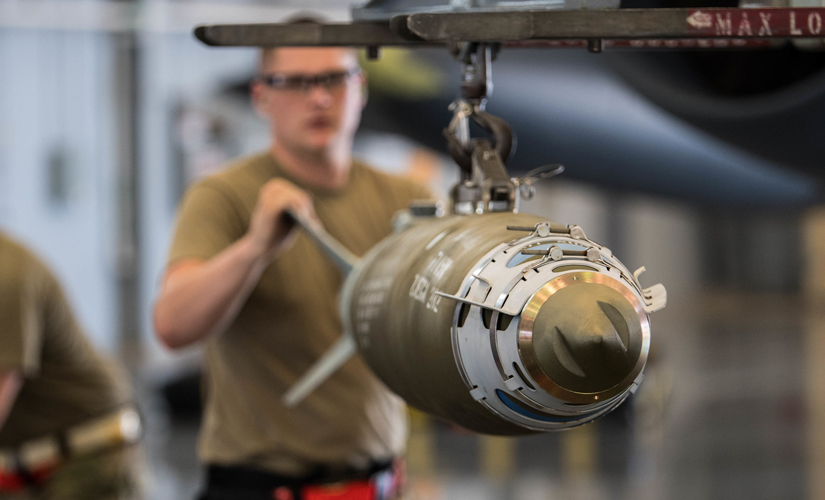 Image of man in khaki shirt and safety goggles working on a bomb. The bomb is pointed towards the viewer and the man stands behind it.