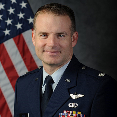 Image of Lt Col Brian Stiles. Stiles is seated before an American flag. He has a closed smile and light hair and is wearing an Air Force uniform with buttons and insignia.