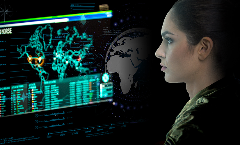 Image of a female in military ware. She is seated in front of a computer screen, which showcases a map of the world and lists/statistics under the map.