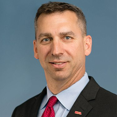 Image of Wes Hallman; Hallman is standing before a blue background, he has a dark suit and red tie. He has light-brown hair and wears an NDIA pin.