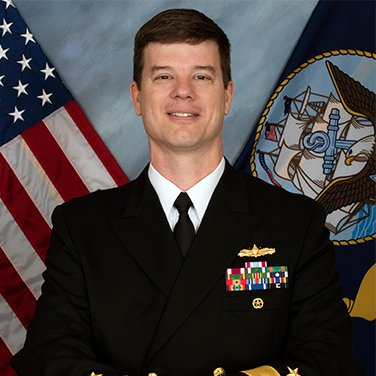 Image of RDML Kevin Byrne, USN who is seated in front of the U.S. and USN flags. He is wearing his navy uniform.