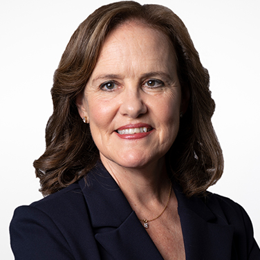 Image of the Honorable Michèle Flournoy. Flournoy is standing in front of a white background. She has light brown hair and is wearing a black blazer. She smiles with her teeth showing.
