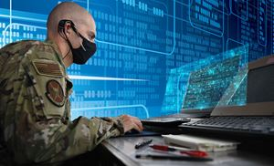 Image of a man in military attire sitting at a computer; he is wearing a face mask.